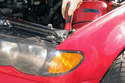 Working at top corner of fender, insert a Phillips screwdriver into hole and remove turn signal lens fastener; some models do not have a screw