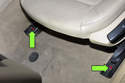 Next, remove two 16mm seat mounting nuts from front seat rail (green arrows).