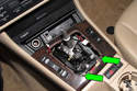 Next, remove two Phillips head screws from center console switch bezel (green arrows).