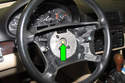 Using a breaker bar with a 16mm socket, remove steering wheel center bolt (green arrow).