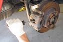 Using a flat-head screwdriver, slowly press brake caliper piston in.