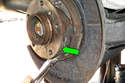 Next, unhook lower return spring from parking brake shoes (green arrow).