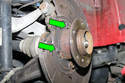 Remove two 10mm backing plate fasteners (green arrows).