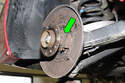Then pull parking brake shoe lever (green arrow) straight out of parking brake cable and remove.