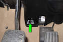 Working at back of trim panel behind brake pedal, unlock trim clip by rotating 90° counterclockwise (green arrow).