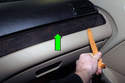 Working at dashboard, using a plastic prying tool lever off right side trim piece (green arrow).