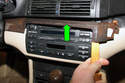 Working at dashboard, using a plastic prying tool lever off radio trim piece (green arrow).