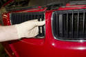 Reach inside inner part of grill to detach retaining clip by prying out and release grill from engine hood.