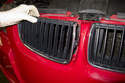 Once clips have been detached, remove grill from engine hood by pulling straight out.