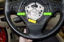 This photo shows the spring (green arrows) you have to lever with the airbag out of the way.