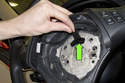 Next, you have to disconnect the steering wheel electronics electrical connector (green arrow) Press the release tab and pull electrical connector straight off.