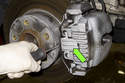 Using a flathead screwdriver, remove brake caliper anti-rattle spring by prying out while securing with hand.