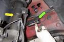 Working behind front strut (yellow arrow), open plastic door (green arrow) for brake pad wear sensor electrical connector.