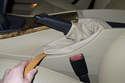 Working in vehicle interior, lever bottom of parking brake lever up using a plastic prying tool.
