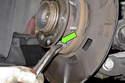Next, unhook lower return spring from parking brake shoes.