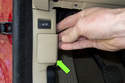 Working at the driver side kick panel, remove the OBD II connector access door.