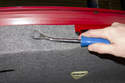 This photo shows removing the center of the rivet using a trim panel tool.