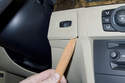 Working at the key slot, lever out the trim cover using a plastic prying tool.