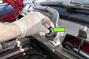 Open hood, then remove the wiper arm nut trim cap.