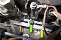 Working at the base of the fuel injector, remove E10 fastener (green arrow) from retainer.