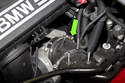 Working at throttle body, loosen intake air duct hose clamp (green arrow) using a flathead screwdriver.