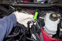 Press hose release (white tab) (green arrow) and pull brake vacuum hose apart.