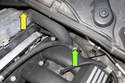 Working at rear of intake manifold, remove fuel line T25 Torx mounting fastener (green arrow), then disconnect crankcase breather hose from valve cover by squeezing collar and pulling off (yellow arrow).