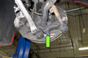Working at steering knuckle, remove 21mm ball joint nut (green arrow).