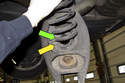When installing new spring, align end of spring (green arrow) with correct spot on insulator (yellow arrow).