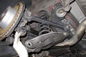 Lift swing arm while lining up coil spring with upper mount.