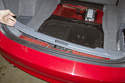 Lift up trunk trim piece and detach it from luggage hooks.