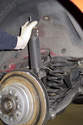 Grab top of shock and slowly compress it until you can remove it from the vehicle.