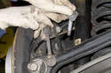Hold sway bar out of the way and remove fastener from traction strut.