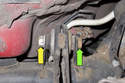 Working at rear of traction strut hold 18mm fastener (green arrow) while loosening 18mm nut (yellow arrow).