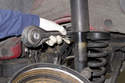 Remove control arm from rear wheel bearing carrier.