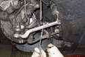 Working at front stabilizer bar, remove stabilizer link nut by counter holding link with a 17mm wrench and loosening 16mm nut.