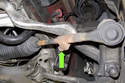 Working at tie rod, loosen T45 Torx pinch bolt (green arrow).