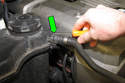 Working at top of coolant expansion tank; using a flatblade screwdriver, release upper hose retaining clip by prying up.