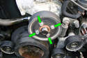 With the mechanical cooling fan and drive belt out of the way remove the four 10mm fasteners (green arrows) that hold the water pump pulley to the water pump flange.