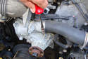Use a flat head screwdriver to loosen the clamp on the water pump for the upper radiator hose and remove the hose.