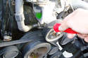 With a small flat head screwdriver loosen the clamp on the small coolant hose and remove the hose on the passenger side of the water pump.