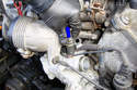 Unplug the electrical connection for the coolant sensor by squeezing the connector and pulling straight up in the direction of the blue arrow.