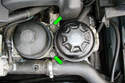 Remove the two 13mm fasteners (green arrows) that mount the reservoir to the oil filter housing and remove the bracket from the reservoir.