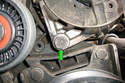 Remove the lower 16mm alternator mounting bolt (green arrow) below the alternator.