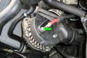 Use a 13mm socket to remove the alternator positive cable mounting fastener (green arrow).