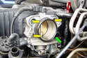 With a 10mm socket remove the four fasteners (yellow and green arrows) recessed inside the throttle body.