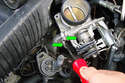 Use a flat head screwdriver to loosen the two clamps that hold the two small coolant lines to the throttle body and pull off the two hoses.