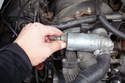 Squeeze the connector for the idle speed motor and unplug it.