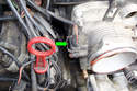 Squeeze the retaining clip on the throttle position sensor (green arrow) and pull the connector towards you to remove the connector from the throttle body.