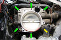 Remove the six T30 Torx fasteners (green arrows) that hold the throttle body onto the intake manifold.